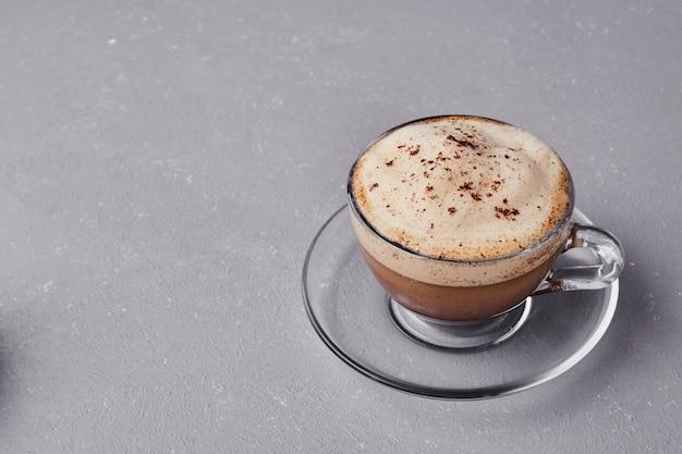 Een kopje melkachtige latte op een grijze achtergrond.