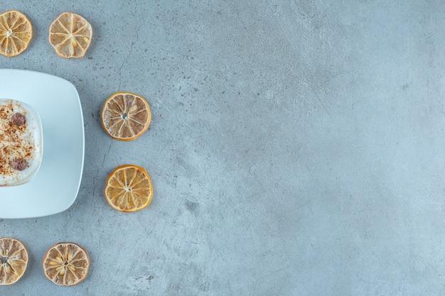 Een kopje melkkoffie naast schijfjes citroen, op de blauwe achtergrond.