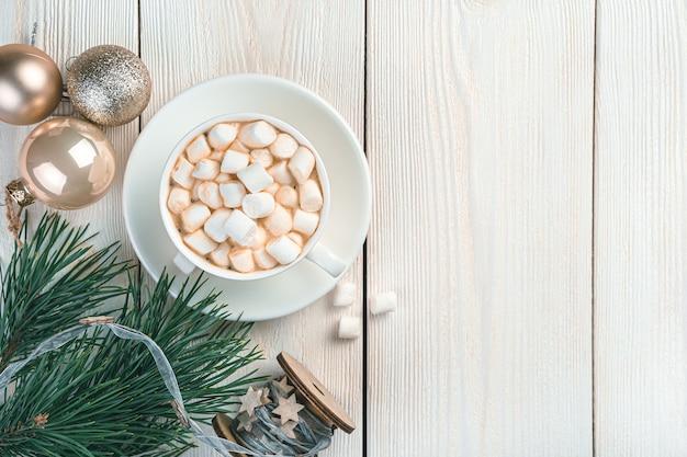 Een kopje met marshmallows, kerstballen en dennentakken op een lichte achtergrond. vrolijk kerstfeest en een gelukkig nieuwjaar. bovenaanzicht, kopieer ruimte.