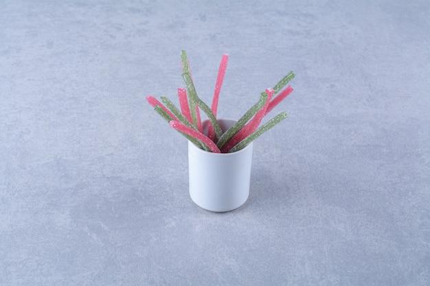 Een kopje met suikerachtige gelei fruit sticks snoepjes op grijze achtergrond. hoge kwaliteit foto