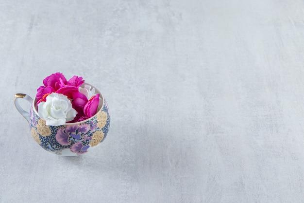 Een kopje paarse en witte bloemen, op de witte tafel.