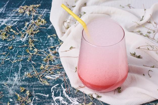 Een kopje roze drankje met zwaar schuim op blauw.