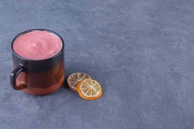 Een kopje roze koffie naast een schijfje citroen, op de blauwe tafel.