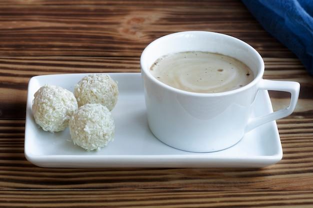 Een kopje schuimige latte staat op een vierkante schotel op een houten tafel met kokossnoepjes