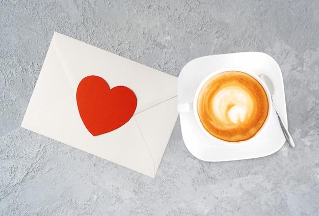 Een kopje smakelijke cappucino en valentijn brief met hart.