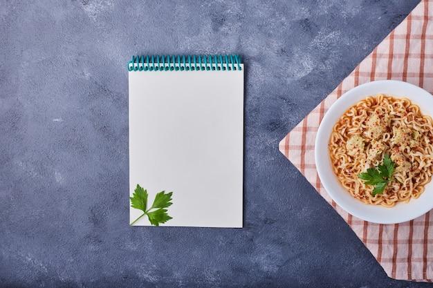 Een kopje spaghetti met een receptenboek opzij.