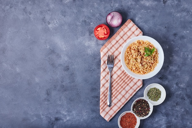 Een kopje spaghetti met kruiden en groenten.