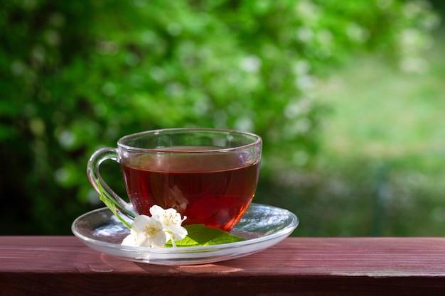 Een kopje thee, een aantal jasmijnbloemen.