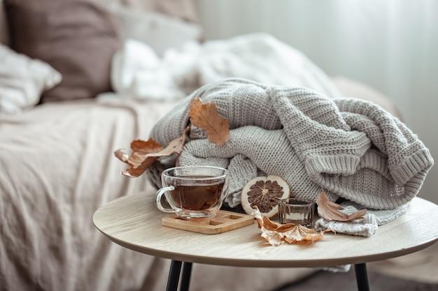 Een kopje thee, een gebreid element en droge herfstbladeren op een onscherpe achtergrond.
