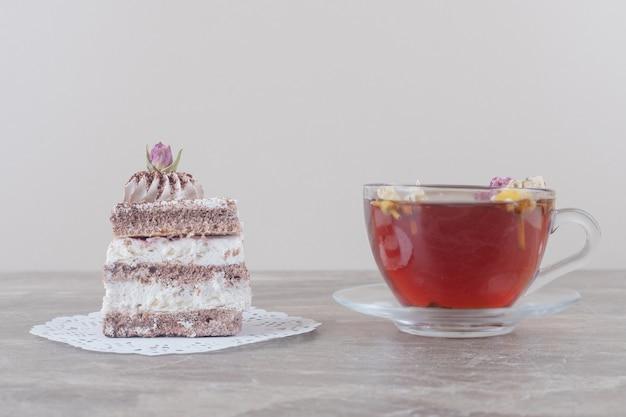 Een kopje thee en een cakeplak op een kleedje op marmer