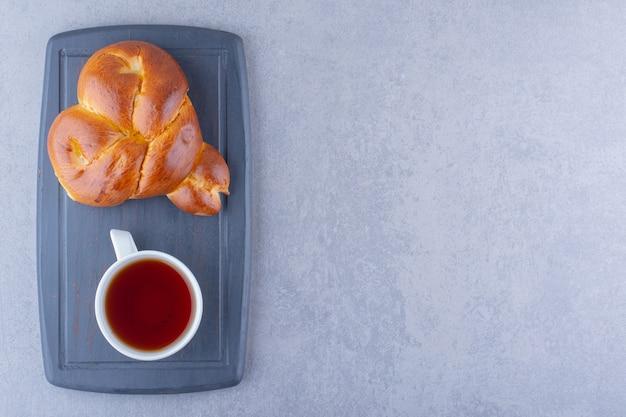 Een kopje thee en een hartvormig zoet broodje op een marinebord op een marmeren ondergrond