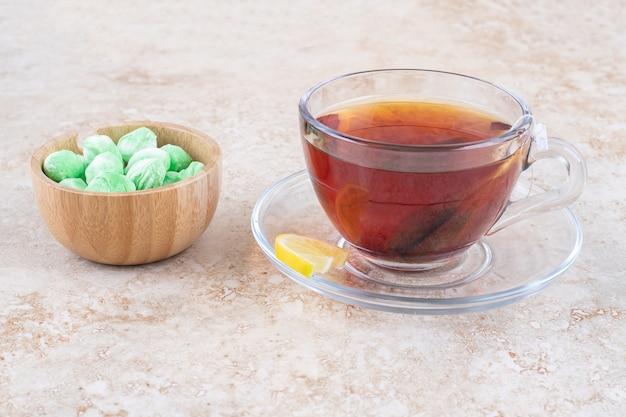 Een kopje thee en een kom met muntsuikergoed