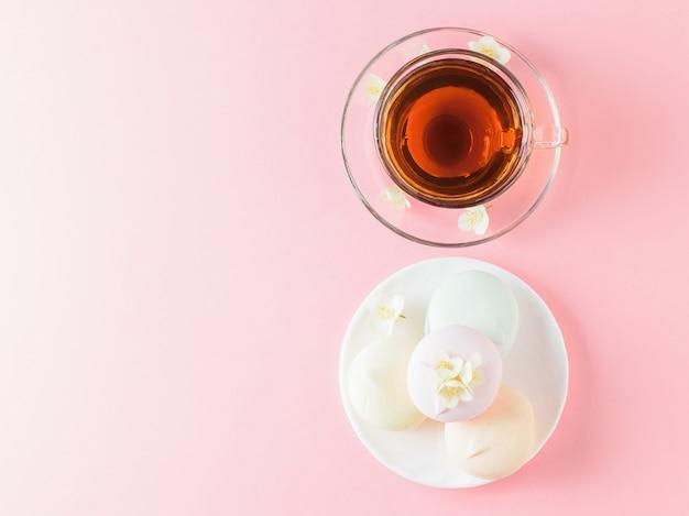 Een kopje thee en een kom van gekleurde marshmallows op een roze tafel. het uitzicht vanaf de top .. de samenstelling van het ontbijt. plat liggen.