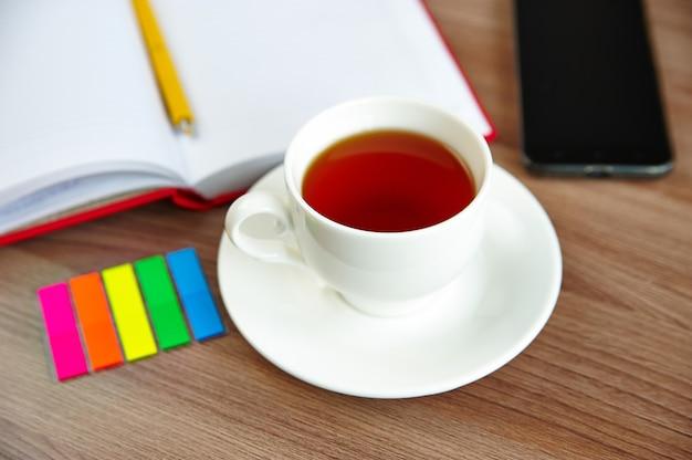 Een kopje thee en een open notitieboekje, een mobiele telefoon op een houten tafel