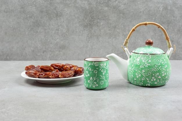 Een kopje thee en een sierlijke theepot naast een bord verse dadels op een marmeren oppervlak. illustratie van hoge kwaliteit
