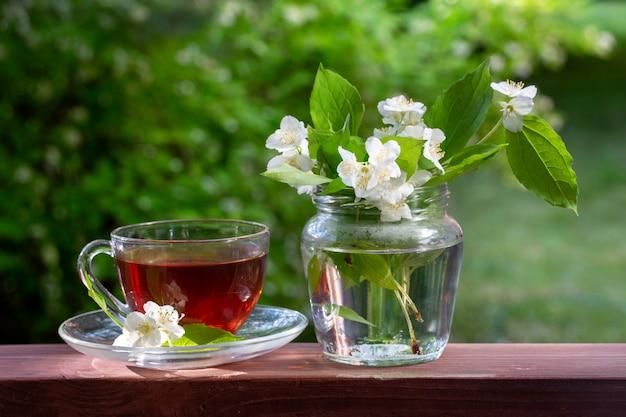 Een kopje thee en een vaas met takjes jasmijn.