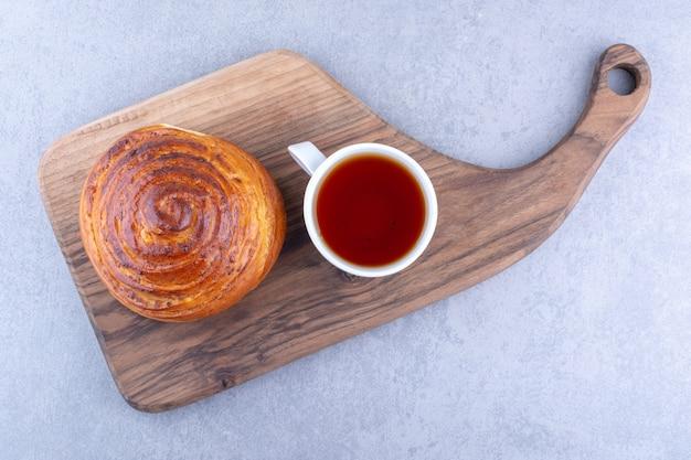 Een kopje thee en een zoet broodje op een houten bord op een marmeren ondergrond