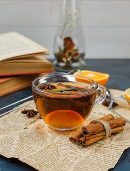 Een kopje thee en kaneel met krant, sinaasappel en een bloemenvaas
