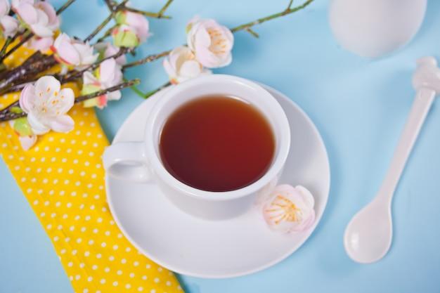 Een kopje thee en kersen bloeien met bloemen sakura op het blauwe oppervlak. lente concept.