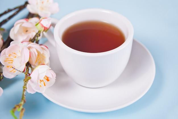 Een kopje thee en kersen bloeien met bloemen sakura op tafel. lente concept.