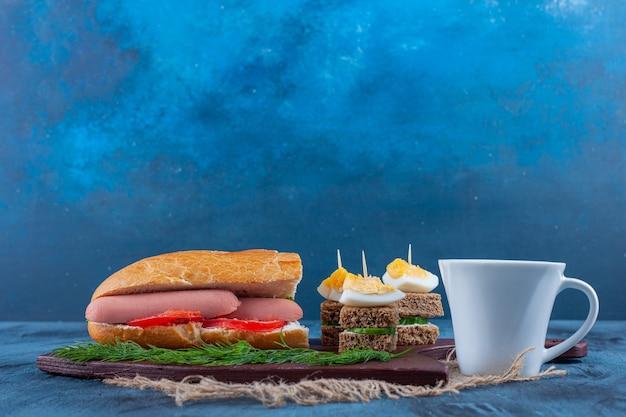 Een kopje thee en sandwich op een snijplank op stof, op het blauw.