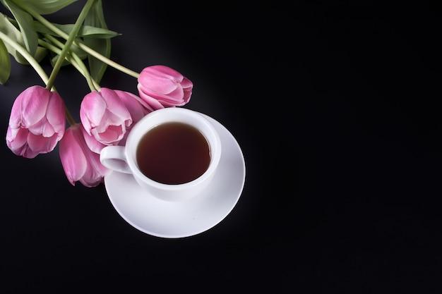 Een kopje thee en violet tulpen op de zwarte tafel. kopieer ruimte. bovenaanzicht.