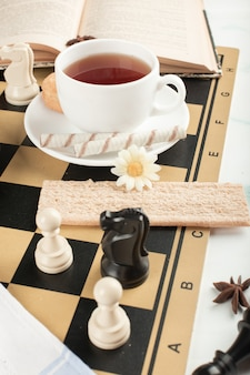 Een kopje thee en wafel op het schaakbord