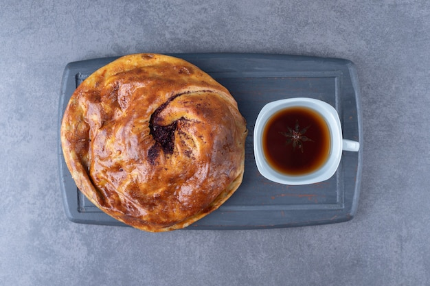 Een kopje thee en zoete taart op een houten dienblad op marmeren tafel.