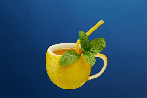 Een kopje thee gemaakt van natuurlijke citroen met muntblaadjes. creatieve compositie rond het thema natuurlijke thee