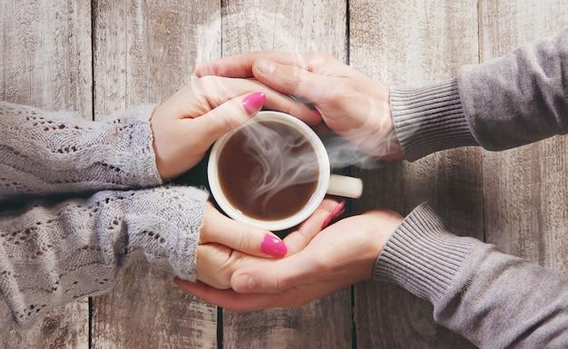 Een kopje thee in de handen van een man en een vrouw. selectieve aandacht.