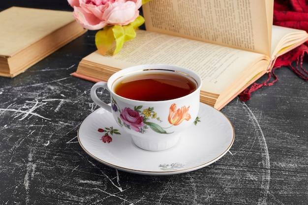 Een kopje thee in een decoratief schoteltje.