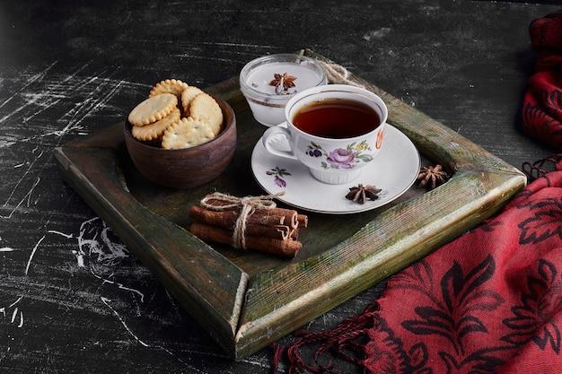 Een kopje thee in een metalen bakje met koekjes.