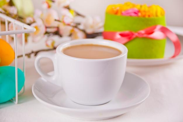 Een kopje thee, kleine lentecake, bloemen sakura, kleurrijke eieren voor pasen. lente concept.