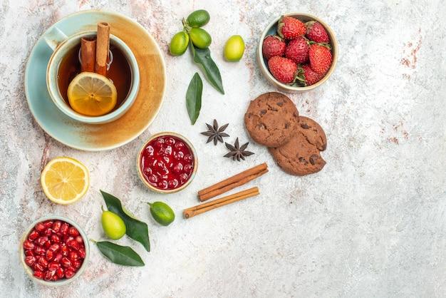 Een kopje thee kommen met bessen citrusvruchten steranijs en kaneelstokjes chocoladekoekjes naast het kopje thee met kaneel op tafel