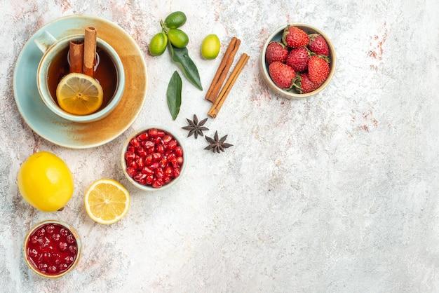 Een kopje thee kommen van bessen citroen steranijs en kaneelstokjes naast het kopje thee met kaneel op tafel