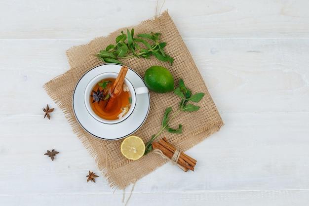 Een kopje thee, limoenen en kaneel in een linnen placemat