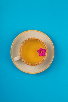 Een kopje thee met bloem op een blauwe achtergrond. minimalistische compositie. bovenaanzicht