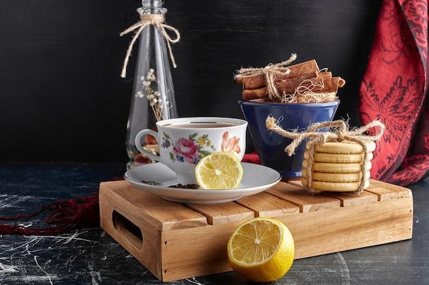 Een kopje thee met citroen, kaneel en koekjes.