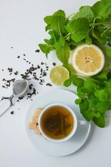 Een kopje thee met citroen, suiker, muntblaadjes bovenaanzicht op een witte ondergrond