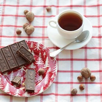 Een kopje thee met een chocoladereep op de geruite handdoek.