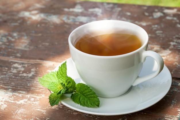 Een kopje thee met een groen blad op een oud houten bord