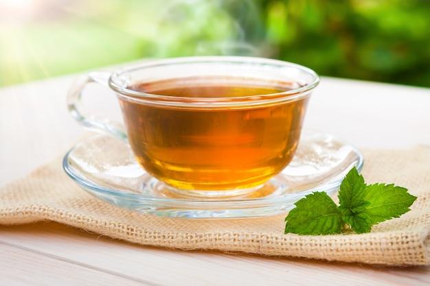 Een kopje thee met een groen blad op oude houten planken en een achtergrond van natuur en platteland