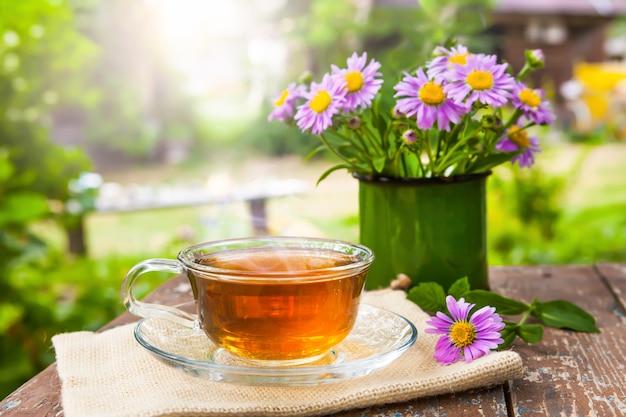 Een kopje thee met een groen blad op oude houten planken met een boeket bloemen
