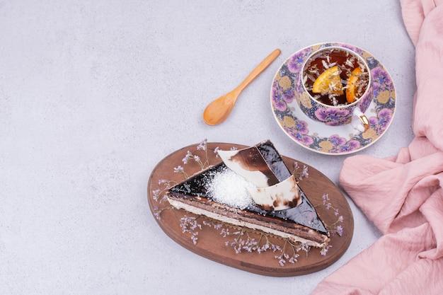 Een kopje thee met een plakje chocoladetaart op een grijze ondergrond