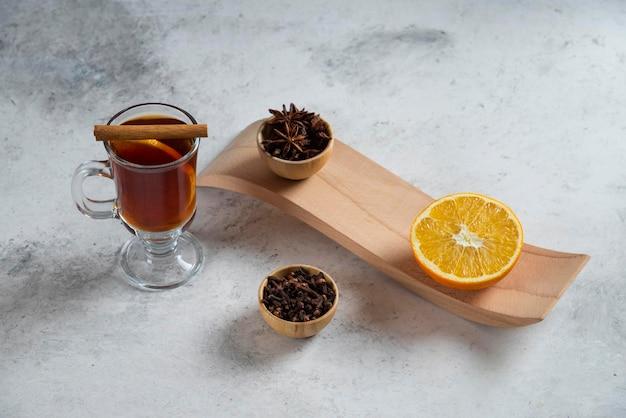 Een kopje thee met een schijfje sinaasappel en gedroogde losse theeën.