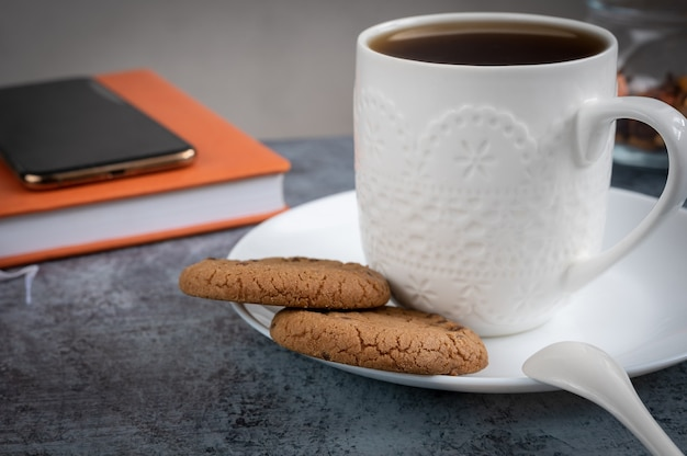 Een kopje thee met koekjes, een agenda en een smartphone op tafel. warm en gezellig interieurconcept