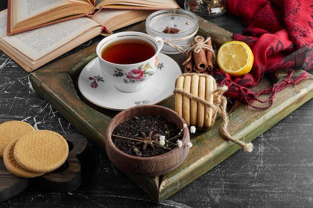 Een kopje thee met koekjes en kruiden.