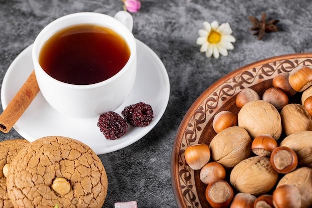Een kopje thee met koekjes en noten. bovenaanzicht