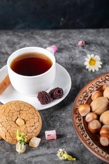 Een kopje thee met koekjes en noten op tafel