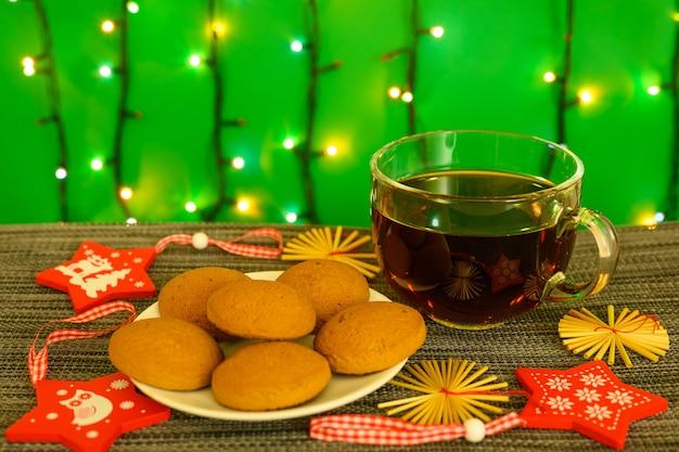 Een kopje thee met koekjes op de achtergrond van een slinger.